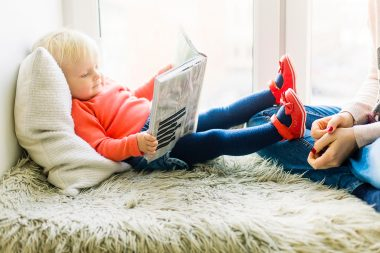 baby reading in window seat